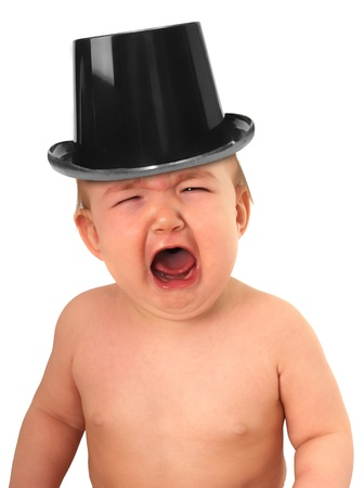 Crying baby wearing a top hat.  photo