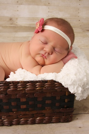 white wood floor: Newborn baby girl asleep in a wicker basket. Stock Photo