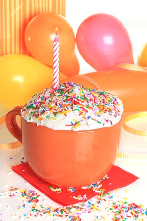 Happy birthday cup cake with one lit candle and balloons. photo