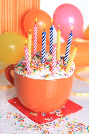 Happy birthday cup cake with lit candles and balloons.  photo