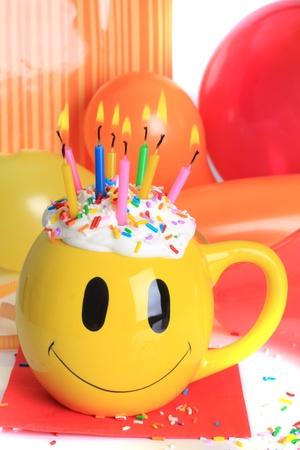 Happy Birthday Smiley Face Tasse Kuchen mit brennende Kerzen und Luftballons.