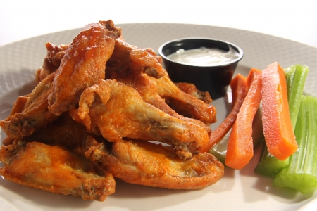 Spicy chicken wings with carrot and celery sticks.  photo