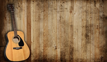 Acoustic guitar against an old barn background.  photo