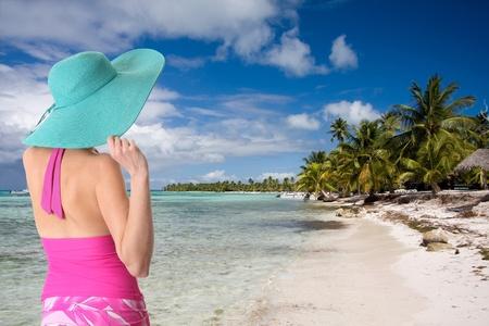 Lady wearing a sun hat on a Caribbean beach Stock Photo