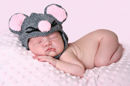 funny baby: Newborn baby girl sleeping wearing a knitted mouse hat.