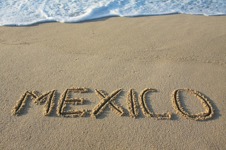 wrote: Mexico written in the sand.  Stock Photo