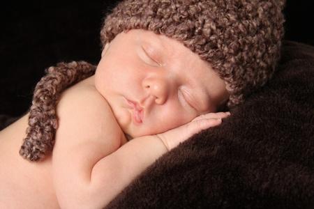 sleep: Newborn baby boy wearing a knitted hat.