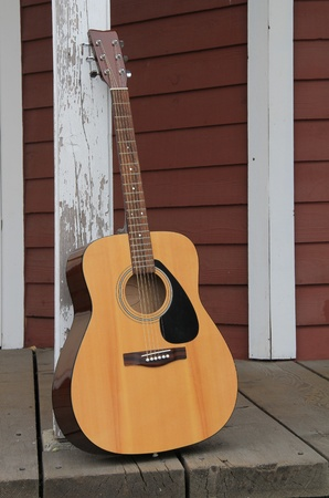 Acoustic guitar leaning against a barn post.  photo