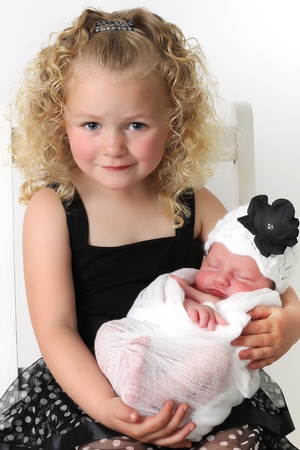 sibling: Beautiful blond girl, holding her newborn baby sister.