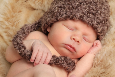 Newborn baby boy asleep on a fur blanket.