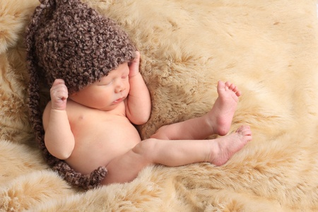 Newborn baby boy asleep on a fur blanket. photo