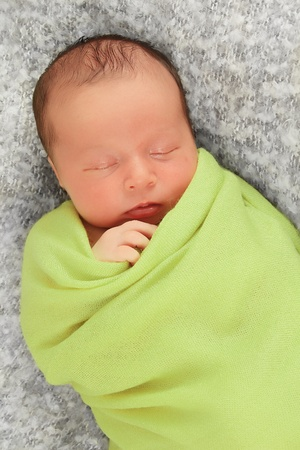 white blanket: Newborn baby boy asleep wrapped in a green blanket. Stock Photo