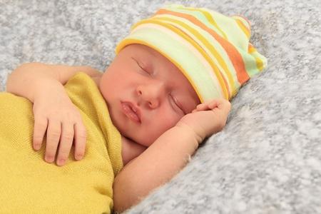 Newborn baby boy asleep wrapped in a yellow blanket.