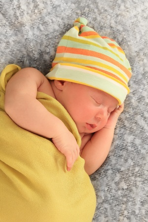 Newborn baby boy wearing a hat, asleep wrapped in a yellow blanket.