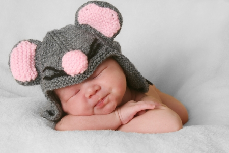 Newborn baby girl sleeping wearing a knitted mouse hat. photo