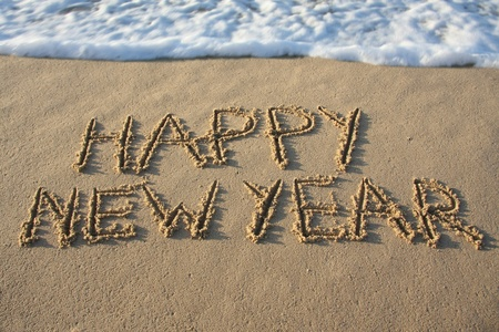 Happy new year written in the sand. Stock Photo