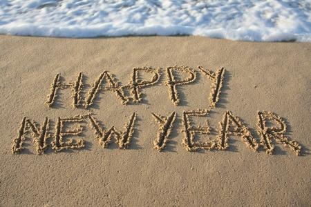 written date: Happy new year written in the sand. Stock Photo