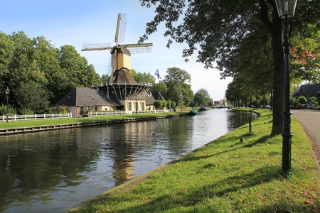 dutch windmill: Picturesque windmill along the canal near Weesp, Holland.  Stock Photo