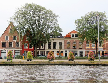 neighbourhood: Colorful Dutch houses along the canal in Haarlem, Holland.
