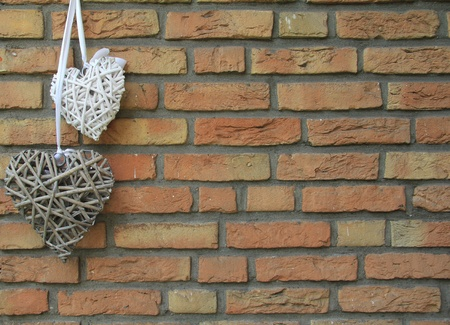 Two woven wicker hearts hang on a brick wall.