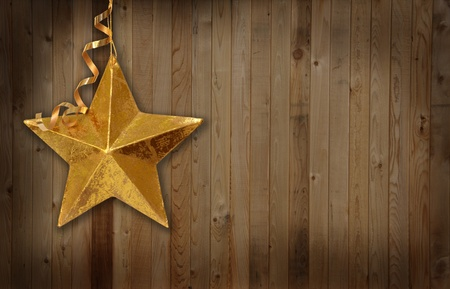 Gold Christmas star agains a wooden country barn background.