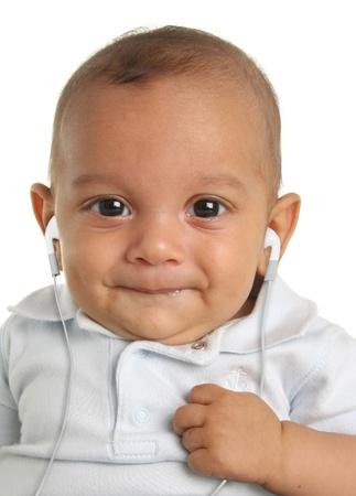 Baby boy luisteren naar muziek op oordopjes. Stockfoto