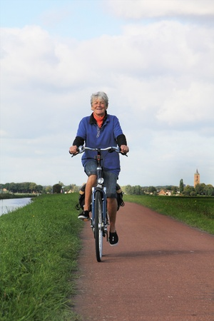 dutch: Seventy year old lady riding a bike in Holland.