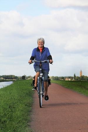 Zeventig jaar oude dame fietsen in Nederland.