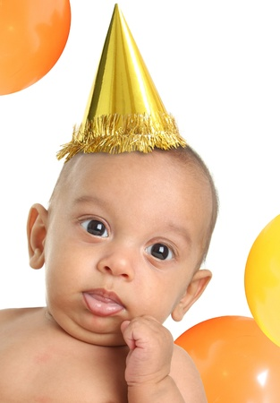 Three month old baby boy wearing a birthday party hat.  Stock Photo