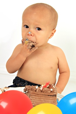 One year old boy eating his first birthday cake.  Stock Photo - 10905529