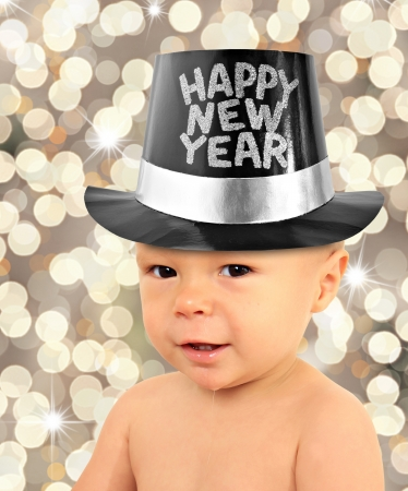 One year old baby boy wearing a Happy New Year top hat.  Stock Photo