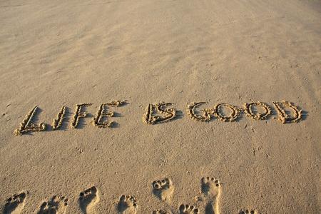Life is good message written on a sandy beach.