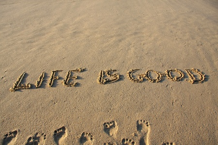 Life is good message written on a sandy beach.