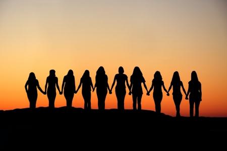 Sunrise silhouet van de 10 jonge vrouwen lopen hand in hand. Stockfoto