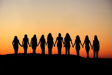 Sunrise silhouette of 10 young women walking hand in hand.  Stock Photo