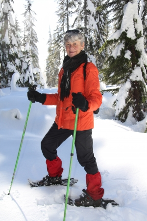 Seventy year old lady having fun snowshoeing on Mount Seymour, Vancouver, Canada.  Stock Photo