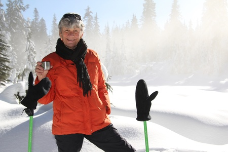 Seventy year old lady having fun snowshoeing on Mount Seymour