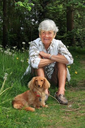 mujeres sentadas: Se�ora Superior de afuera con su perro salchicha. Foto de archivo