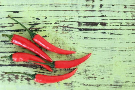 Chili peppers on a rustic wood background   photo