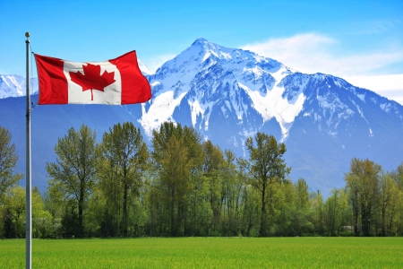 Canadian flag in front of te snow capped Rocky Mountains, British Columbia, Canada   Stock Photo