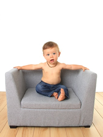 Adorable ten month old baby boy seated on a sofa chair   photo