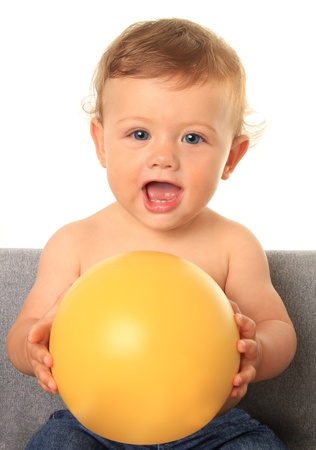 Adorable ten month old baby boy holding a yellow ball   photo