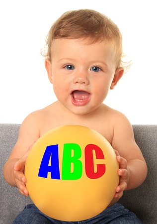 Adorable ten month old baby boy holding a yellow ball with ABC photo