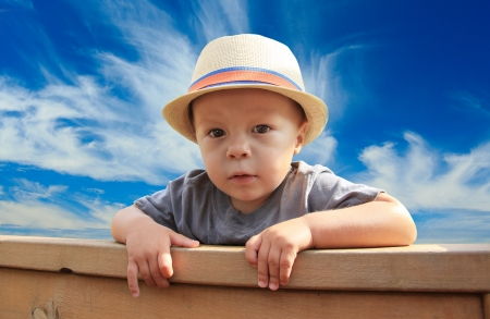 Young boy peeking over a fence   photo