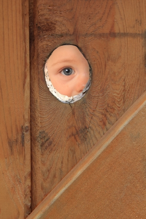 Young boy with blue eyes peeking through a hole in a fence. Stock Photo - 14880809