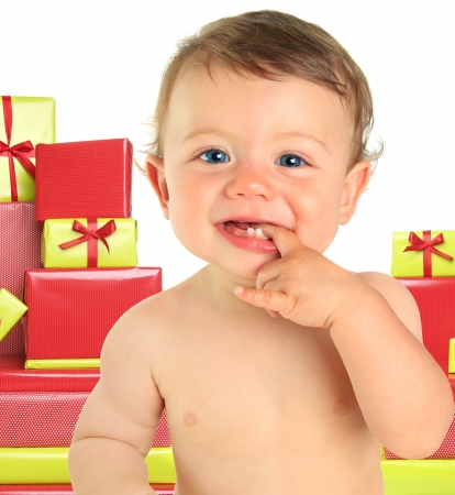 Adorable ten month old baby boy surrounded by Christmas gifts.  photo