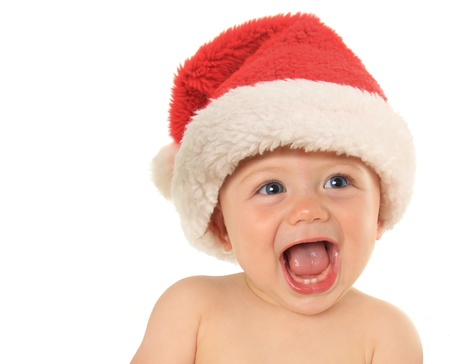 Adorable ten month old baby boy wearing a Santa hat