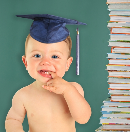 Adorable ten month old baby boy wearing a mortar board in front of a black board and a stack of books   Stock Photo - 15435495