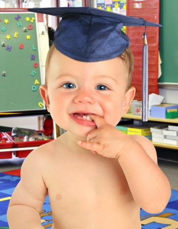 Adorable ten month old baby boy wearing a mortar board in front of a black board and a stack of books  photo