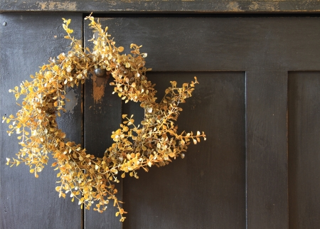 Yellow wreath hanging on vintage wooden door.  photo